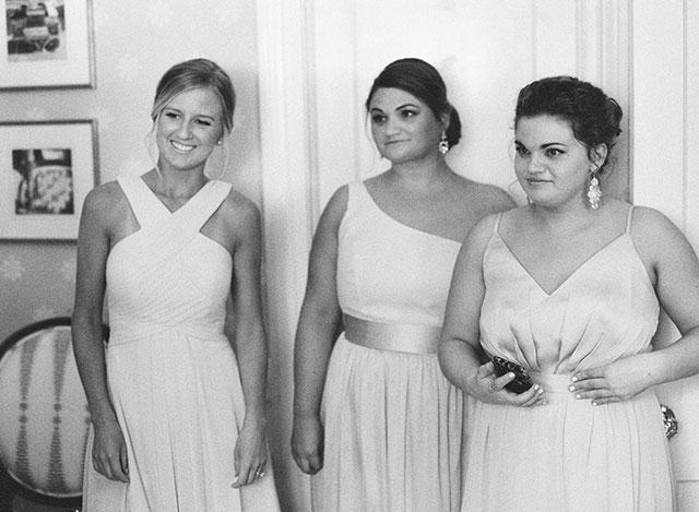 bridesmaids watching as bride buttons dress