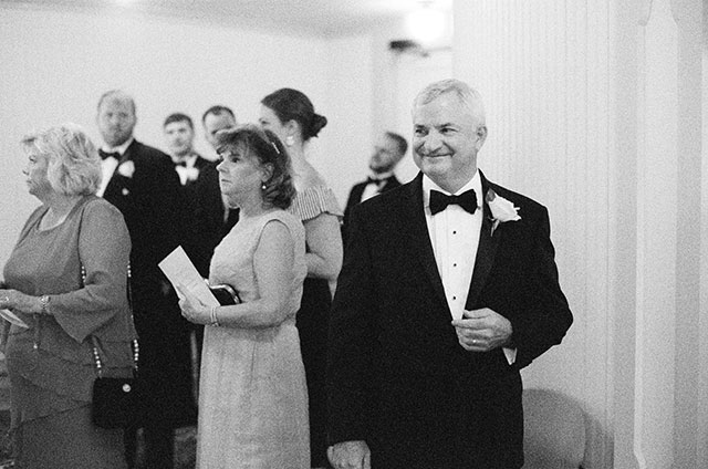 father of the bride smiles as he waits for the ceremony to begin