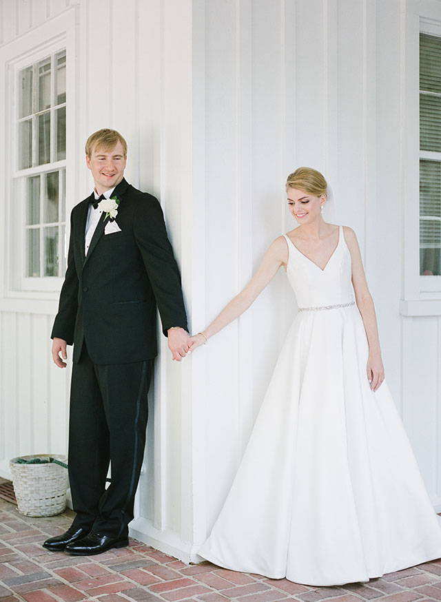 St. Mary's Episcopal Church first look, bride and groom hold one anothers hands around a corner by Sarah Der Photography