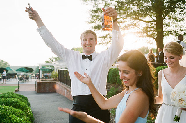 Film wedding photography of groom digging up bourbon on wedding day by Sarah Der Photography