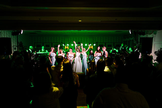 bride and bridesmaids on stage singing aretha franklin