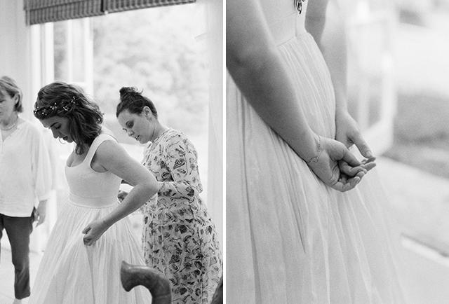 black and white MF film photo of bride putting on wedding dress - Sarah Der Photography