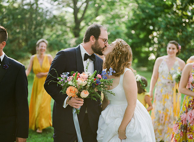 bride and groom kiss with bridal party in background - Sarah Der Photography