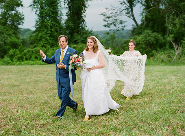 bride cries as her father walks her down the aisle