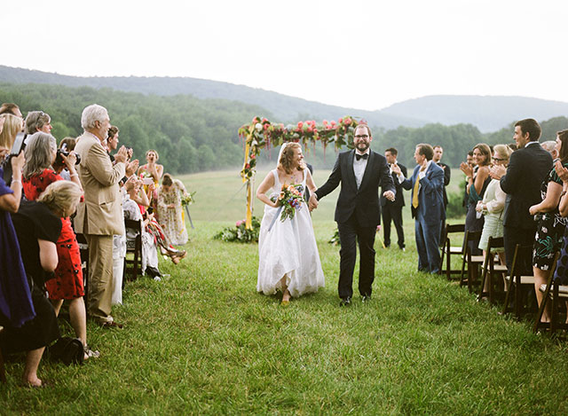 couple walks down the aisle with mountains in the background