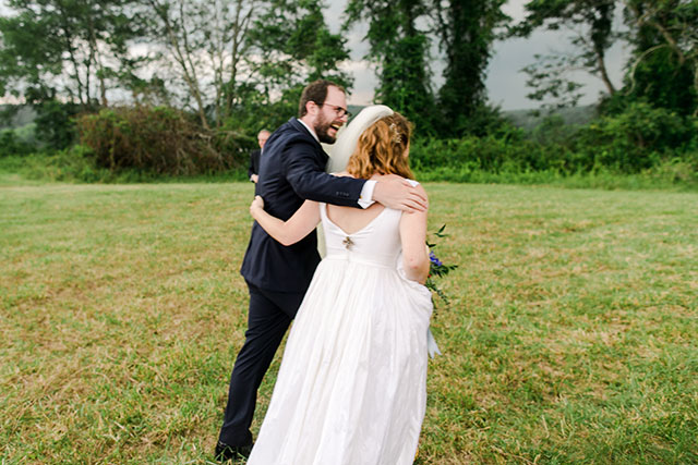 couple laughs and walks with grooms arms around her shoulders
