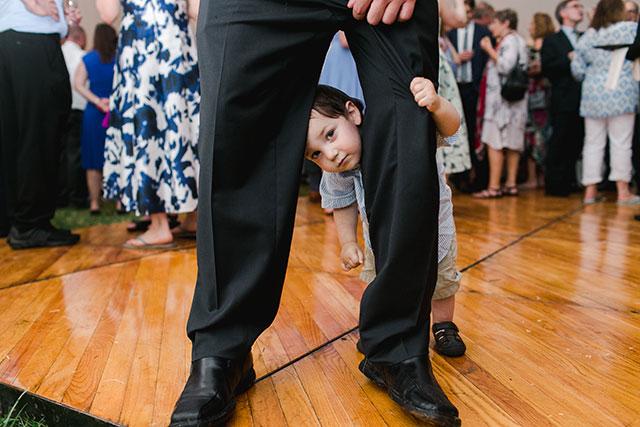 little boy hides under dad's legs