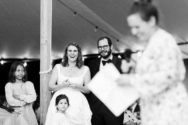 black and white candid photo of couple during toasts