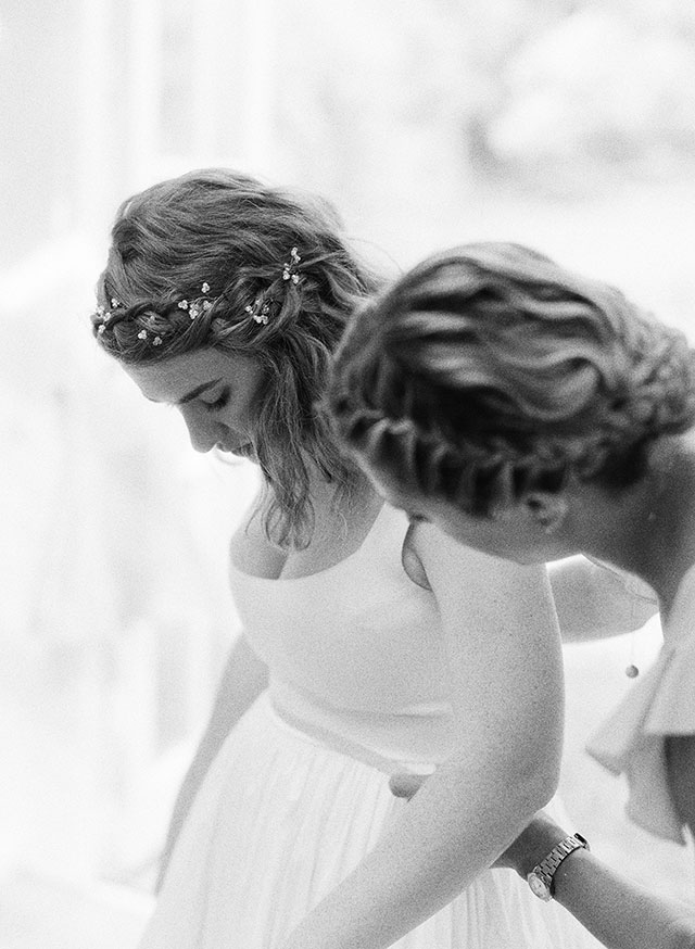black and white film wedding photo of bride putting on wedding dress