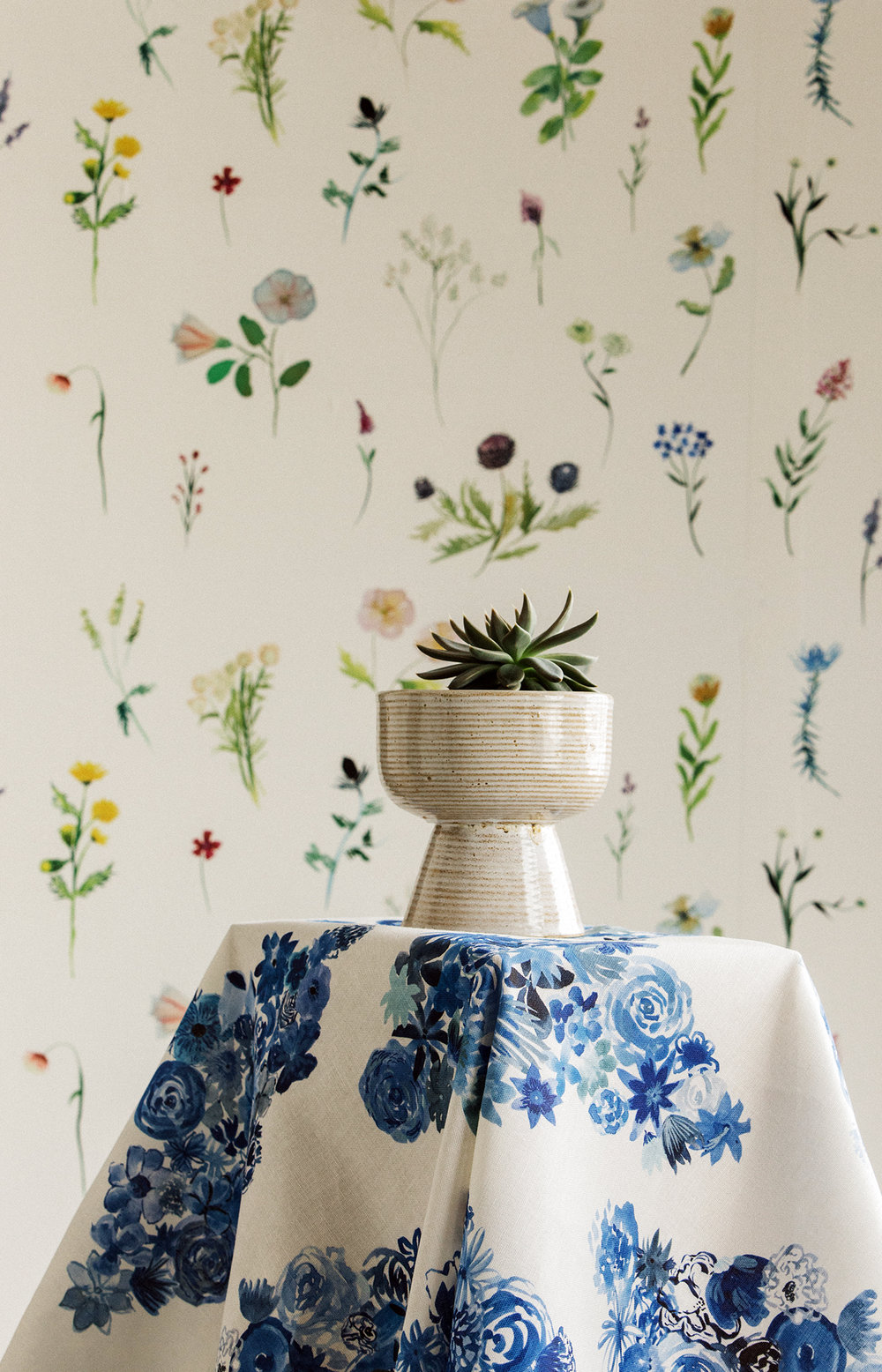 """""""Flora"""" in 'Casbah Blue' fabric in front of """"Meadow"""" in 'Heliotrope' wallpaper."""