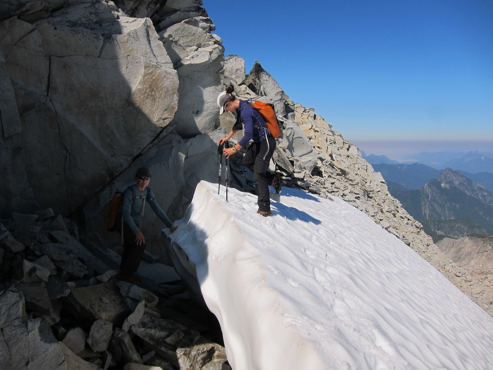 Mom about to step up onto a steep snow ledge just below the Mt. Hinman summit.