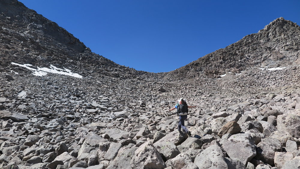 Picking our way (slowly) through an endless sea of boulders to Raid Peak Pass (low point in the distance).