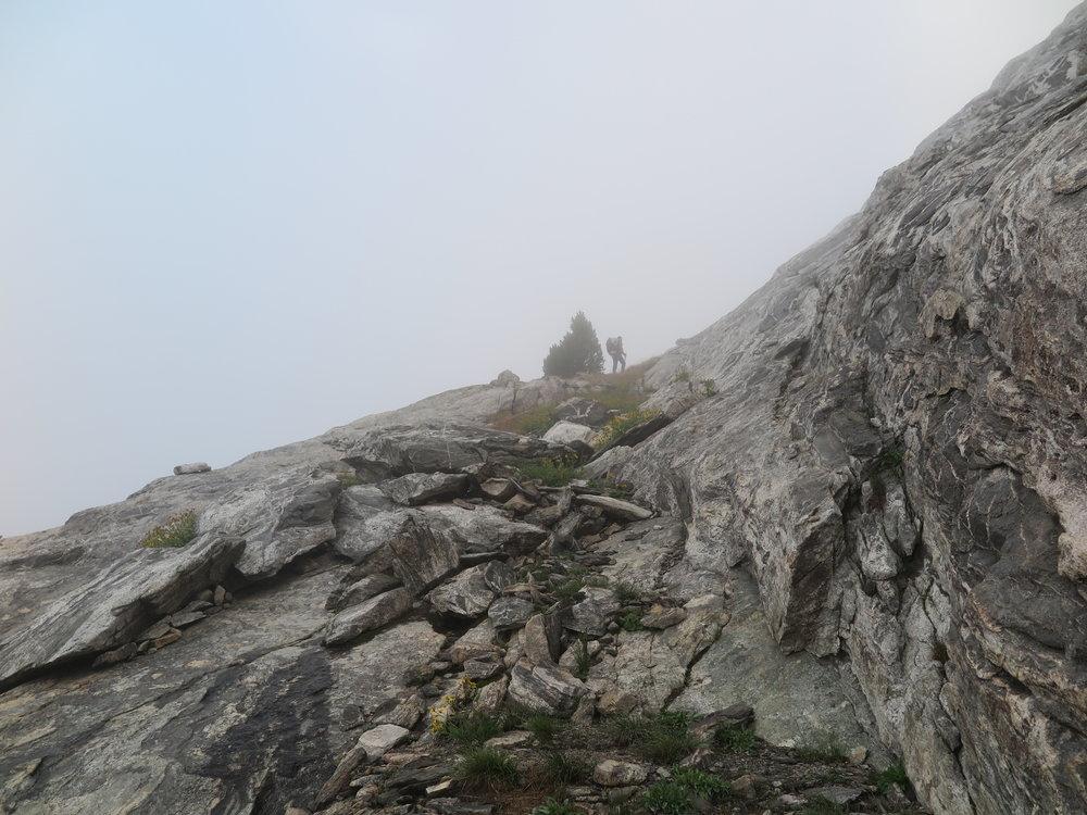 Slowly picking our way through the fog up the ledges towards Europe Peak.