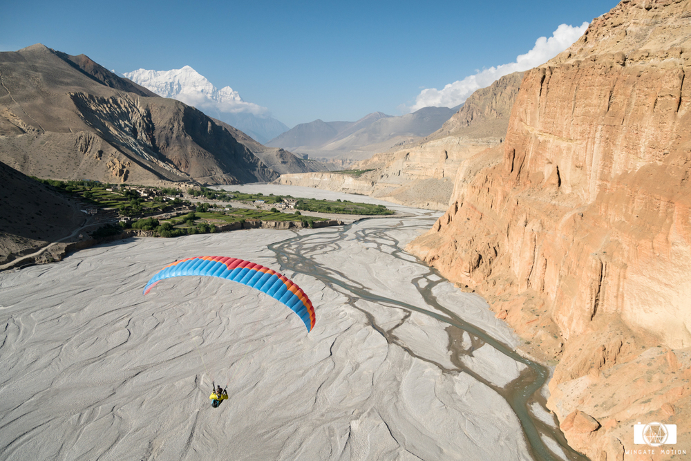 Jamie Messenger descends into the river valley with views of 8000m Annapurna 1 in the background. Photo: Nick Greece