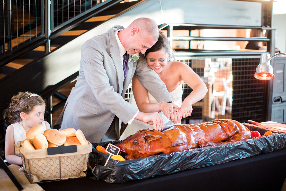 bride and groom cutting the pig roast