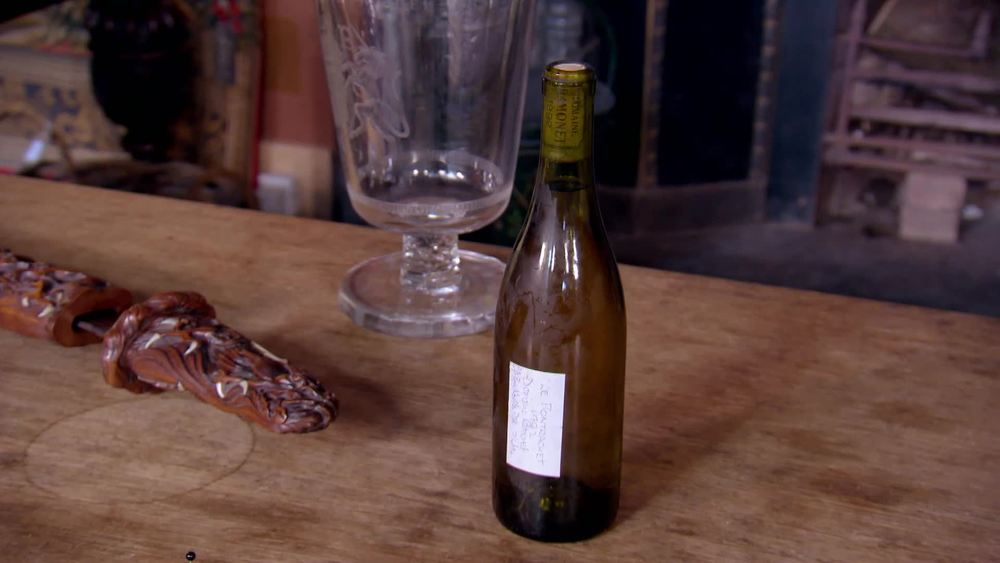 "Unlabelled bottle of wine. Branded cork ""Domaine Ramonet Le Montrachet"" £2000 