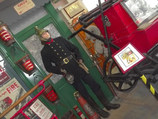 1890's. Victorian Fireman's Uniform Men's Mannequin First fireman's uniform introduced 1833 grey jacket and trousers with knee high boots and a black leather helmet.