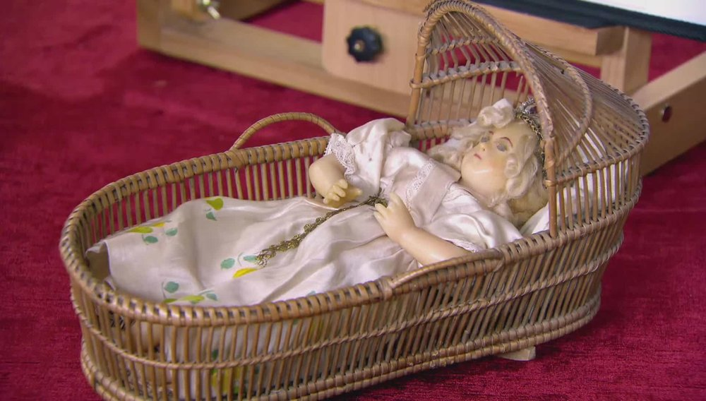 An early wax Doll in basket. Porcelain headed dolls are far more collected and so more valuable. Price: £100 PRIVATE COLLECTOR