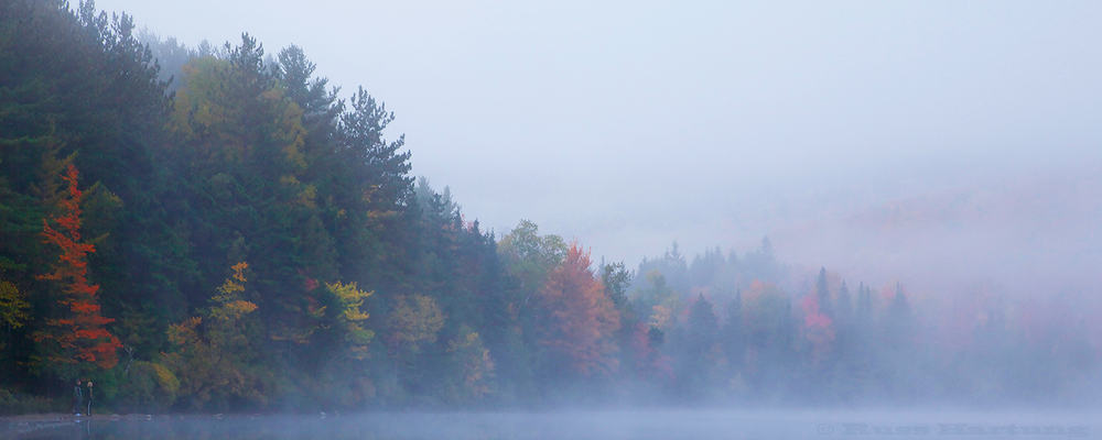 A couple enjoys the morning mist and the fall colors at Heart Lake in the High Peaks region of the Adirondacks.