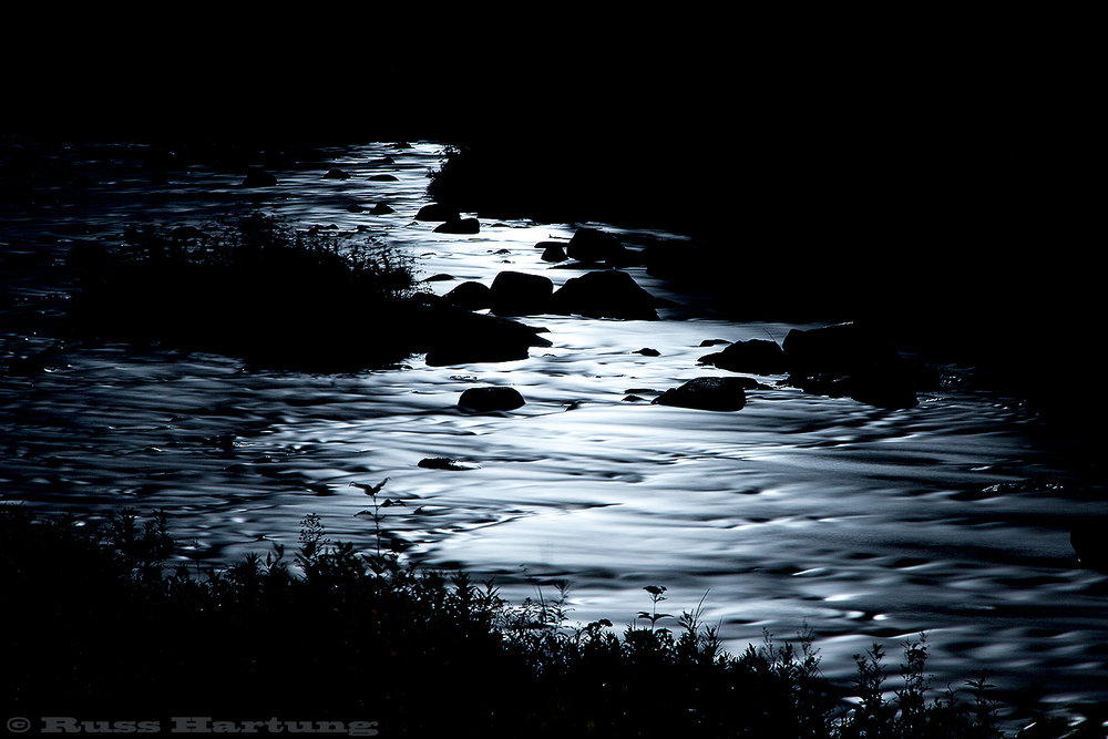 The Saranac River under the moonlight. A long, 3-minute exposure made the rapids look like molten silver.