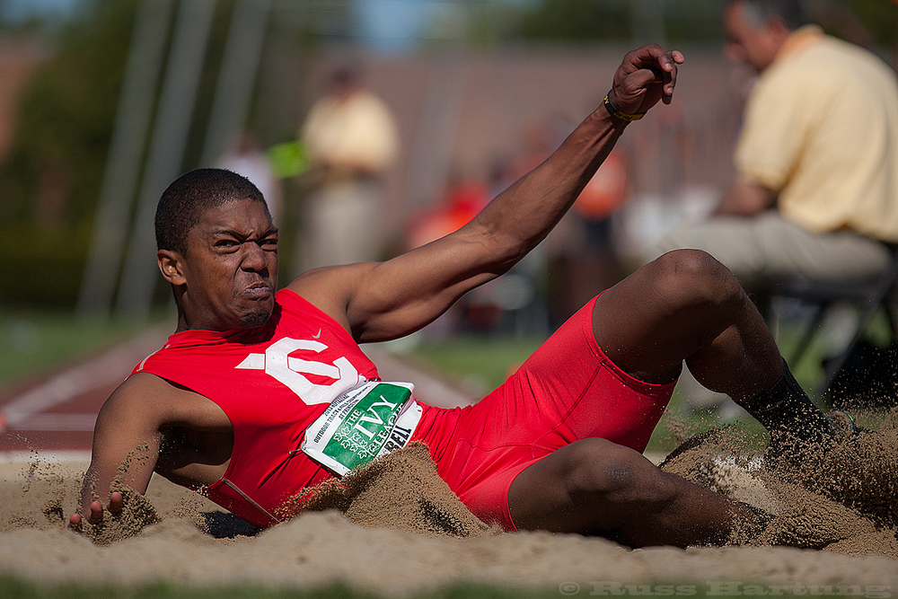 Steven Bell lands in the sand pit during the long jump competition at the Heptagonal Championships.