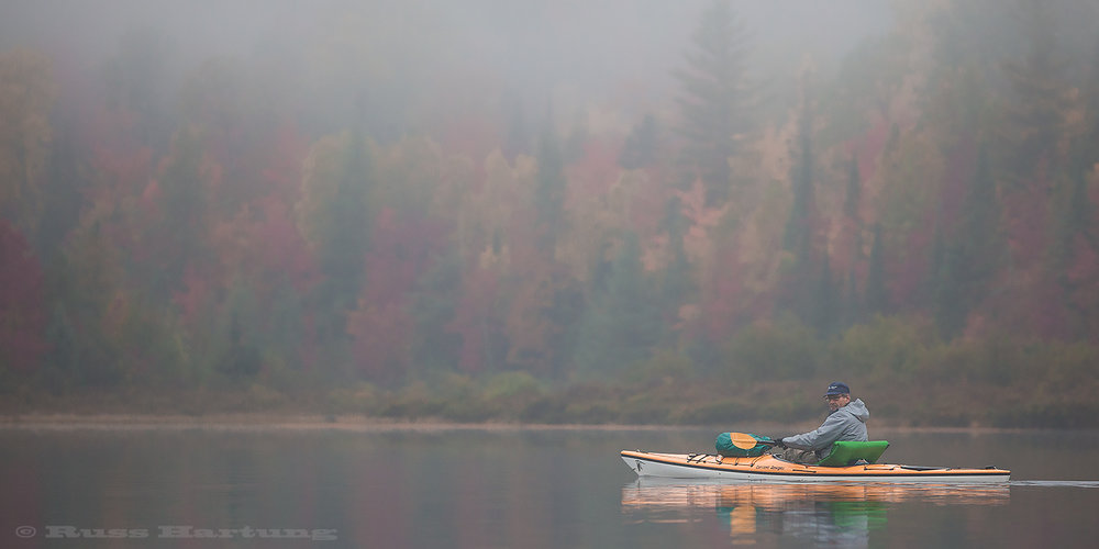 My friend Gary paddling across a foggy Cheney Pond during peak foliage season.