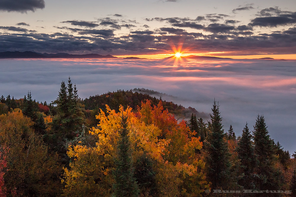 The first rays of the sun skip across the fog to spotlight the foreground trees on Goodnow Mountain.