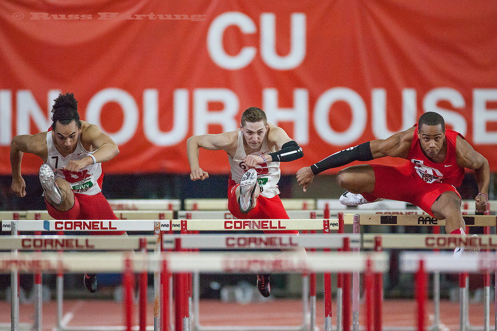 Two hurdlers are in synch while a third edges slightly ahead.