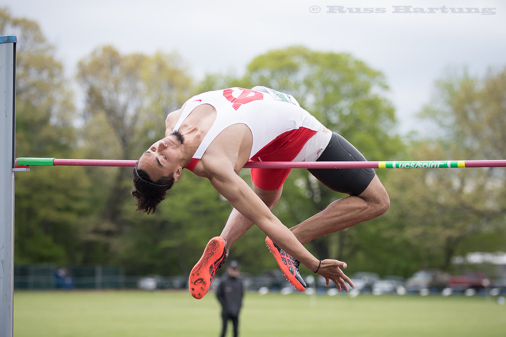 A high jumper near folds himself in half to clear the bar.