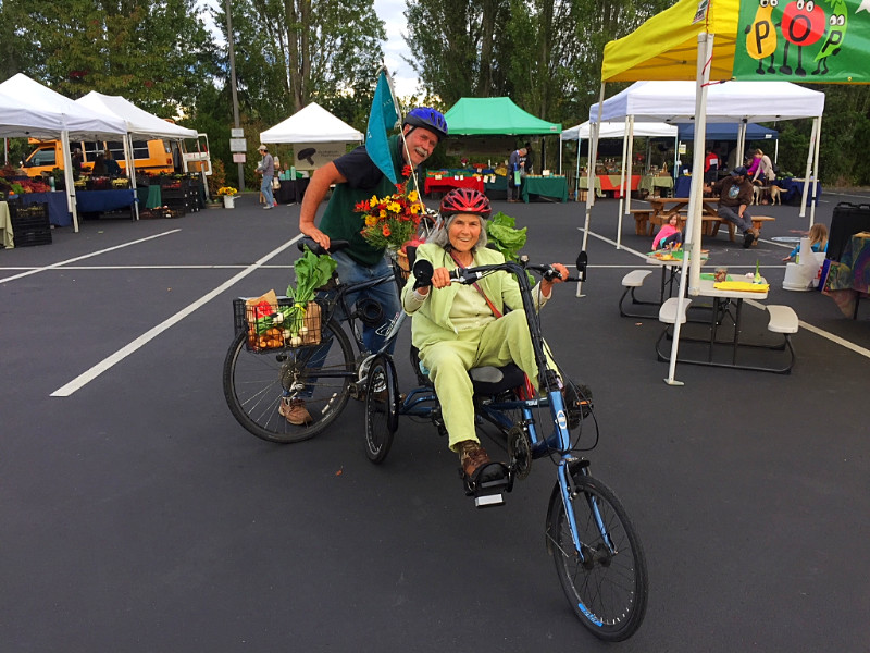 Nancy and Doug Milholland on bike at the Port Townsend Wednesday Farmers Market.