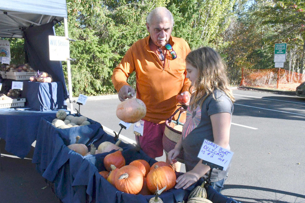 Laila Garrison, 8, and her grandfather Vern Garrison, decide on which Kuri squash to take home from the Wednesday market. Laila said she liked the market very much and was hoping for a pumpkin. She plans to find one at the Saturday market in a few weeks. (Jeannie McMacken/Peninsula Daily News)