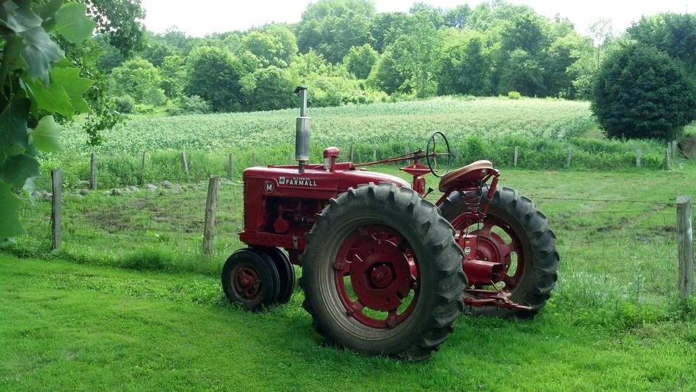 red tractor with corn field behind.jpg