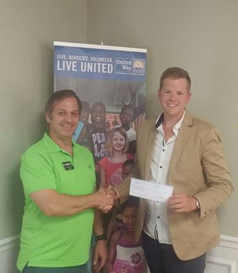 Brian Vinciguerra owner of Cracked It! Escape Games presents a check for the Onslow County Stuff the Buss Campaign. The Escape Room dedicates 10% of it's Monday and Thursday proceeds to local charities via it's #GIVEBACK initiative.