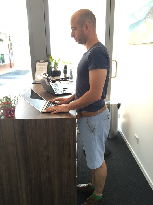 Yanek showing good standing posture at a desk