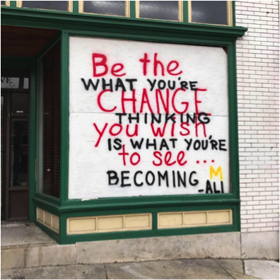 "Image: Graffiti in a shop window that says ""Be the change you wish to see"" and ""What you're thinking is what you're becoming"""