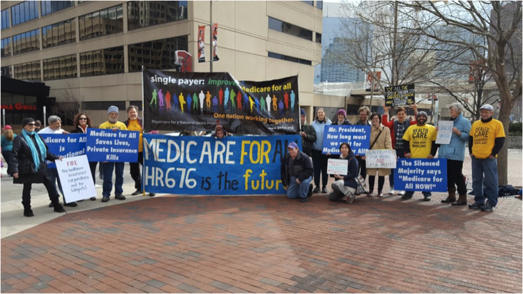 "Healthcare Is A Human Right Maryland supporters pose for a group photo holding signs that say ""Medicare For All HR676 is the future"", ""Medicare For All Saves Lives, Private Insurance Kills"", and ""Single payer: improved Medicare for all""."