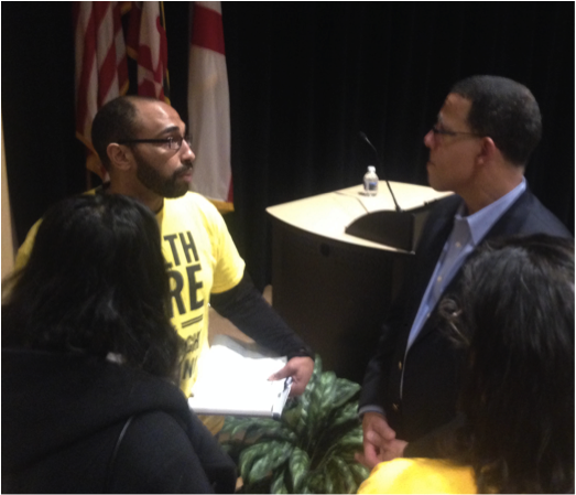 Chapter Leader Phil Ateto speaking with Rep. Anthony Brown at a town hall meeting
