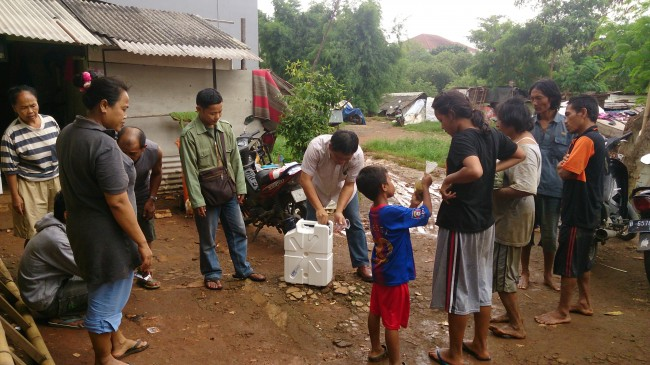 Robby Reppa of Wadah Foundation demonstrating the correct usage of the Jerrycan Lifesaver to the residents of Kali Bekasi as accompanied by Adi hermawan, the coordinator of Kali Bekasi Community