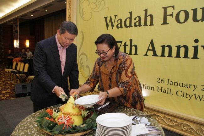 Mrs. Anie & Mr. Hashim Djojohadikusumo cutting the rice cone during the 7th Anniversary of Wadah Foundation.