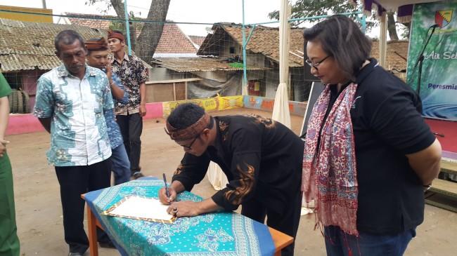 Kepala Desa Arjasari, Bapak Rosiman, menandtangani sertifikat peresmian pompa air
