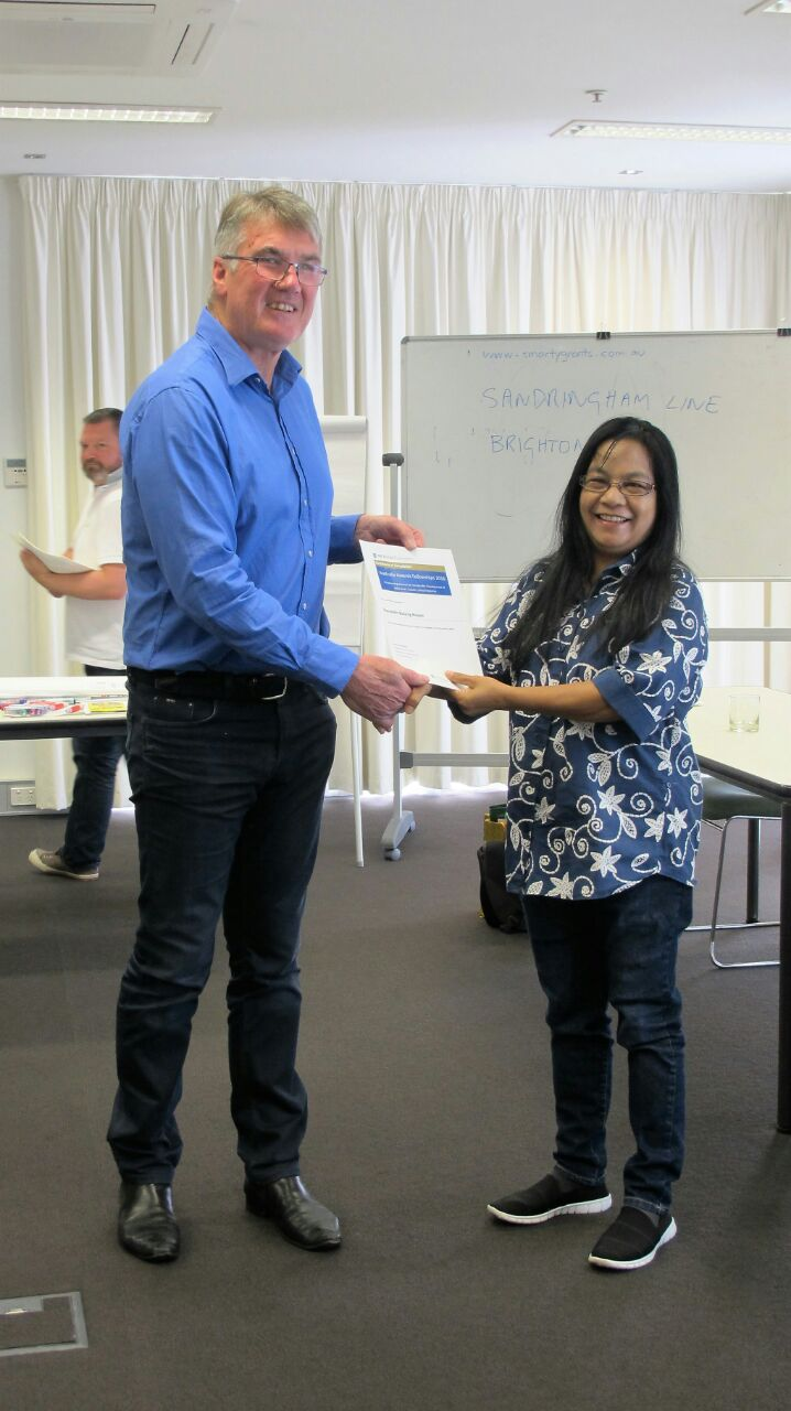 Ibu Oa receiving her certificate of participation