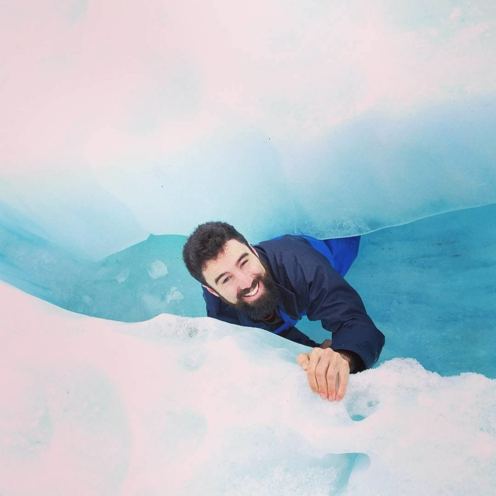 Climbing through an ice cave on Fox Glacier.