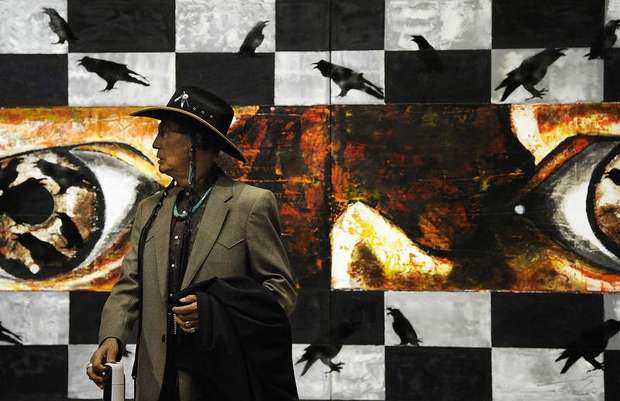 Russell Means standing in front of Gerald Cournoyer's painting in the Center for Western Studies at Augustana College on Friday, April 27, 2012. Photo by Jay Pickthorn - Sioux Falls  Argus Leader