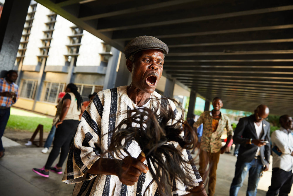 A man sings of his hope for a peaceful Liberia outside Monrovia's supreme court.