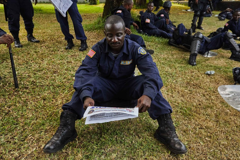 Liberian officer reading the days election news.