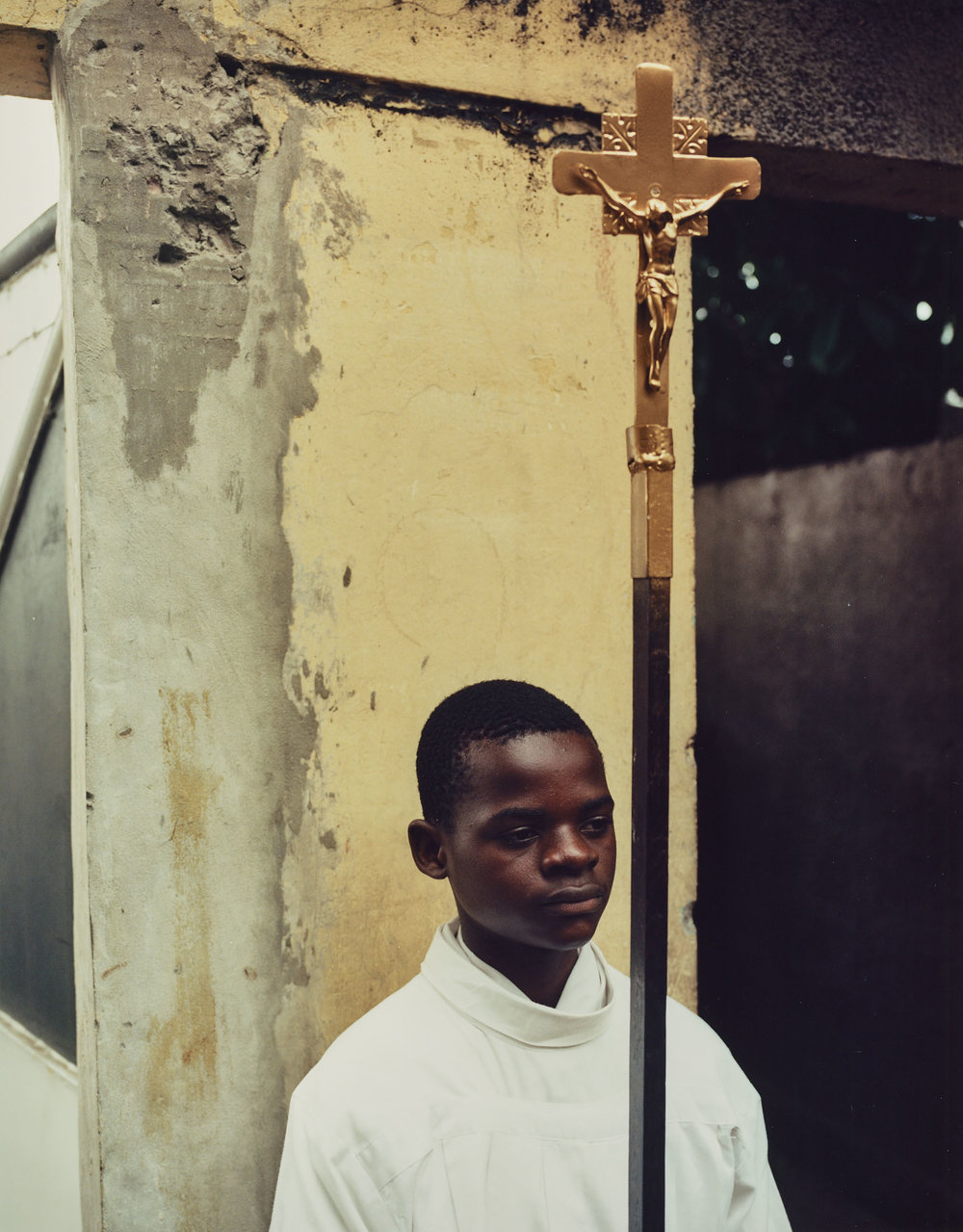 Muzina di Tata, E di Mwana   A young acolyte holds the cross of St. Dominique before Sunday service.