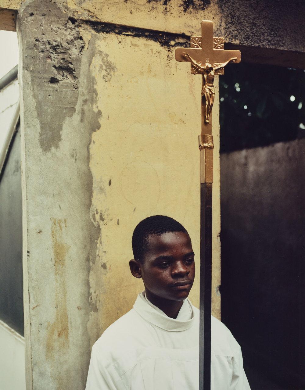 Muzina di Tata, E di Mwana   A young acolyte holds the cross of St. Dominique before Sunday service.