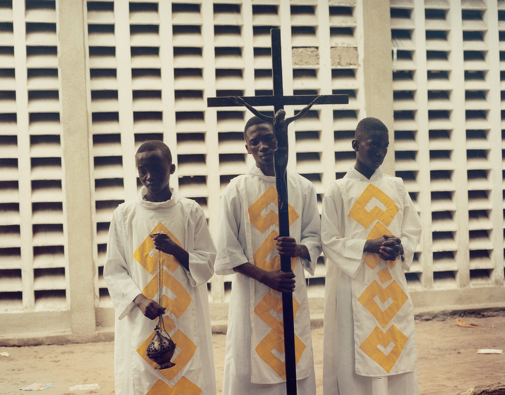 Acolytes Kumu, Maleba and Booto hold the ceremonial cross of La Paroisse St. Benoit, Lemba, Kinshasa.