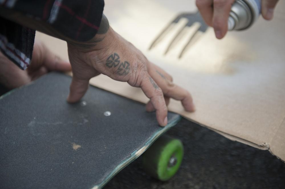 "Rich Facun holds down his stencil while Moss Miller spray paints his board with the ""fork crew."""