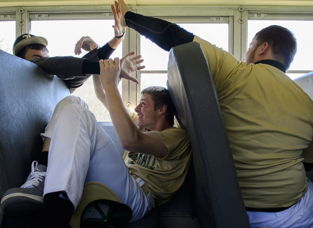 "Brendan Sano and Colter Thompson team up on Ryan Luehrman to bug him and interrupt his sleep on the bus ride to Vinton County High School. Thompson was reading The Adventures of Huckleberry Fin until Sano shouted, ""Colter help me!"" Thompson turned around and helped Sano torment Luehrman. While boarding the bus for the ride home, Sano joked with Luehrman and told him to sit in front of him. Luehrman said laughing, ""No way, I'm sitting in the back."""